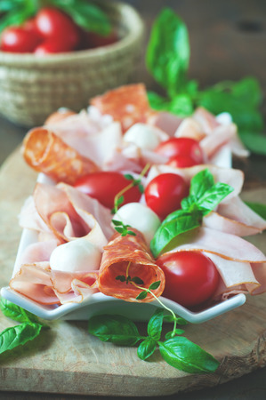 Ham, salami, antipasto, mozzarella and bocconcini soft cheese, fresh tomatoes on wooden background, selective focus, toned image
