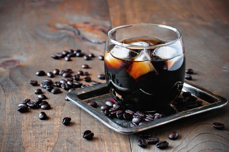 Liqueur in glasses with coffee beans on a wooden background, alcoholic Mexican drink, selective focus, toned image 스톡 콘텐츠