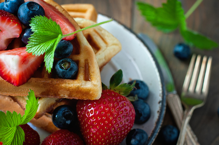 Belgian waffles with strawberries, blueberries and syrup, homemade healthy breakfast, toned image, selective focus