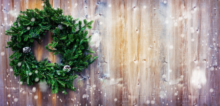 Christmas fir wreath on wooden background. Toned image. Copy space. Long format for web design. Stockfoto