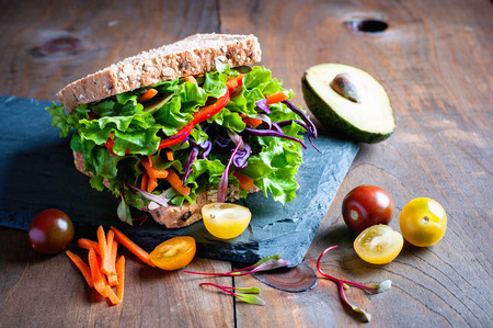 Vegan wholegrain sandwich with ingredients for healthy meal,  avocado, micro greens, super food, diet concept, selective focus, toned image