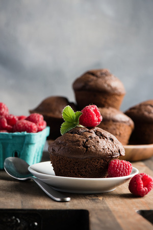 Chocolate muffins or cupcakes with raspberries, healthy breakfast, homemade snack, selective focus, toned image.