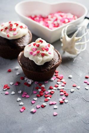 Chocolate muffins or cupcakes with heart sprinkles. St. Valentines day baking. Selective focus, toned image. Stockfoto