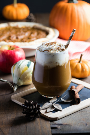 Pumpkin latte with spices, coffee autumn of fall drink with pumpkins, Thanksgiving table, copy space, selective focus