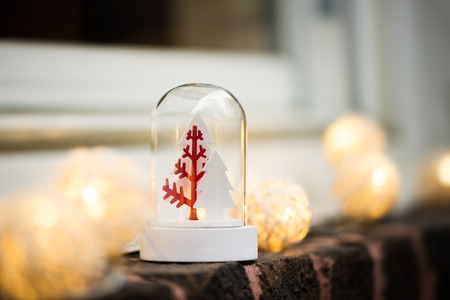 Christmas snow globe with trees and lights on a window, brick wall. Copy space