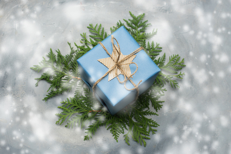 Christmas gift box in blue wrapping paper. Copy space. Toned image, falling snow effect.