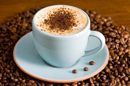 cappuccino op tafel met koffiebonen Stockfoto