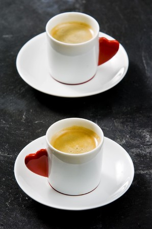 Espresso served on heart shaped cup on coffee beans photo