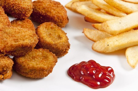 Chicken nuggets on white plate with ketchup and french fries Stockfoto