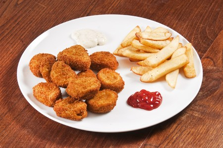 Chicken nuggets on white plate with ketchup and french fries photo