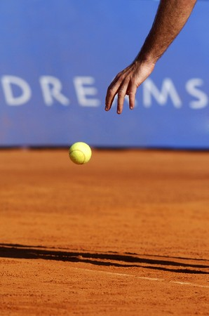 Man with tennis ball on a clay court photo