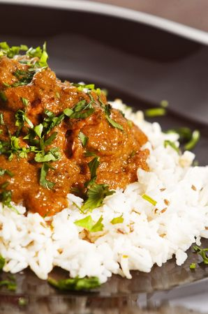 кинза: Chicken tikka masala served  with rice and garnished with cilantro leaves