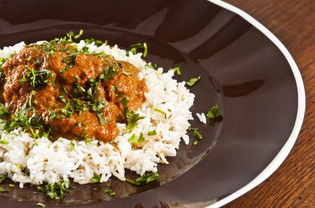 curry chicken: Chicken tikka masala served  with rice and garnished with cilantro leaves