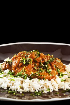 Chicken tikka masala served  with rice and garnished with cilantro leaves photo