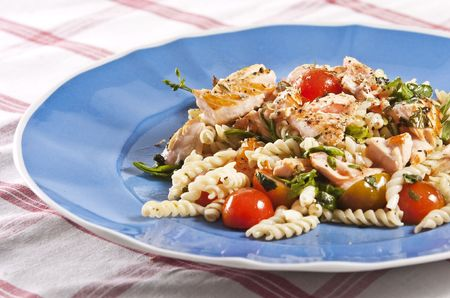 grilled salmon on blue plate with tomato and arugula pasta salad photo