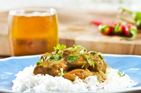 masala: Chicken curry served  with rice and garnished with cilantro leaves Stock Photo