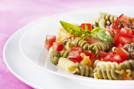 Pasta primavera garnished with basil leaves photo