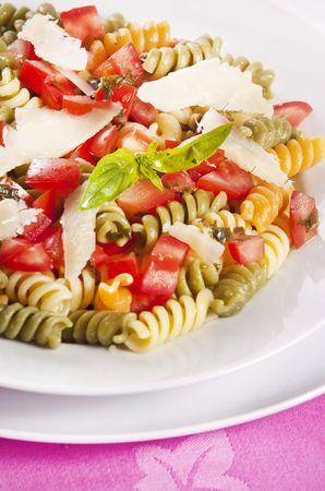 Pasta primavera garnished with basil leaves photo