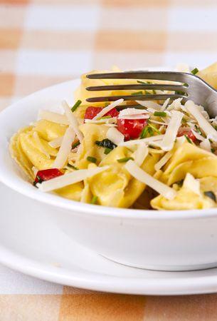 primavera: Tortellini primavera garnished with basil leaves on white plate