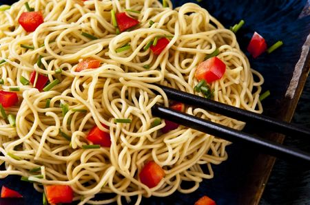 Chinese noodles with vegetables served on a blue dish Stockfoto