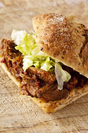 pulled: Delicious pulled pork sandwich on wood board