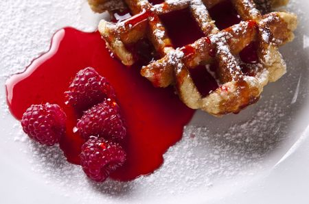 Delicious Belgian waffles garnished with fresh raspberries photo