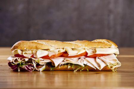 deli sandwich: Turkey sandwich with cheese lettuce and tomato