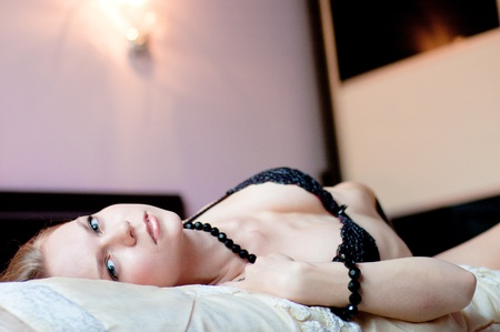 The beautiful girl lies on bed in a bedroom, dressed in linen, looks in the camera.
