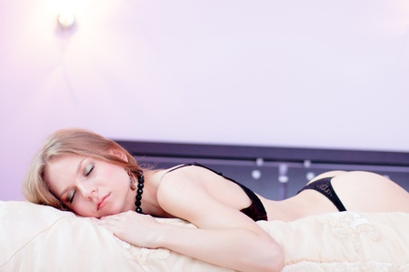 wery sexy woman sleep on a bed in bedroom dressed in a linen.  Stock Photo