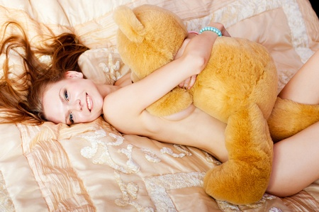 pretty nude woman lies on bed and embreces a teddy bear