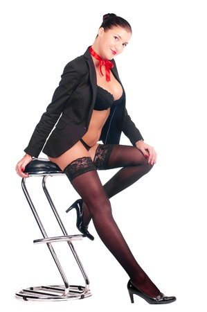 The beautiful sexy girl sits on a bar chair in stockings and a black jacket with a red bow on her neck photo