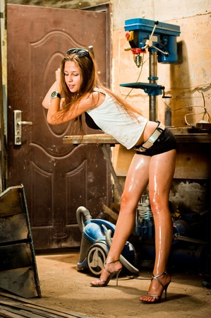 Woman in dirty t-shirt working with tools in garage Stock Photo - 8629463
