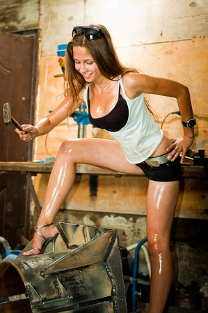 Woman in dirty t-shirt working with tools in garage