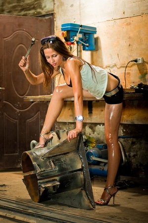 Woman in dirty t-shirt working with tools in garage photo
