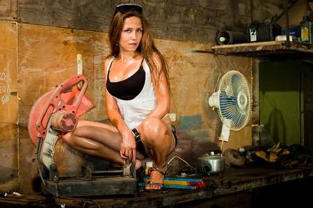 Woman in dirty t-shirt working with tools in garage Stock Photo - 8629464