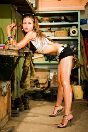 Woman in dirty t-shirt working with tools in garage Stock Photo - 8629424