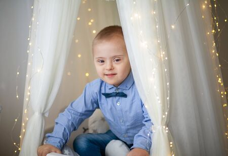 Portrait of a boy with Down Syndrome. Genetic and mental illness in a disabled child.