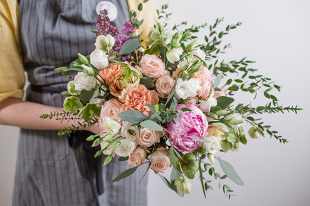 Rich bunch of pink peonies and white eustoma roses flowers, green leaf in glass vase. Fresh spring bouquet. Summer Background. Florist with flowers. bouquet in hands