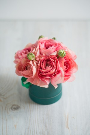 persian buttercup: bunch of pale pink ranunculus persian buttercup  light background, wooden surface. glass vase.  green box  spring, summer