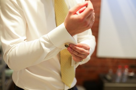 cufflink: close up of a hand man how wears white shirt and cufflink. yellow tie