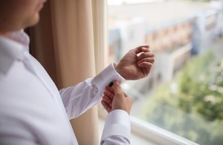 cufflink: close up of a hand man how wears white shirt and cufflink. window wiev Stock Photo
