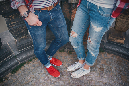 warm weather: Young couple in love standing on the street in gumshoes in summer sunny warm weather. Stock Photo