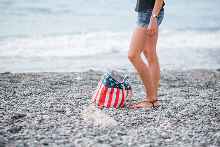philosophy of music: girl stand in the beach. Usa flag bag.