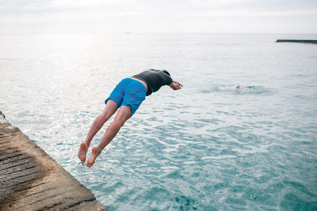 drowns: Young man jumping into water. save life. man drowns