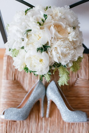 diamante: wedding shoes and wedding bouquet of white roses. Stock Photo