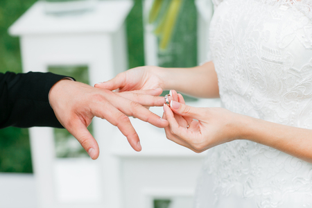 wedding customs: Close-up of a bride putting a wedding ring on a groom Stock Photo