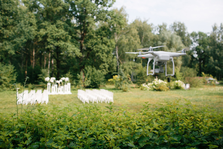 Videography wedding ceremony from the air a small spy quad copter scout drone flying through the trees in a forest.