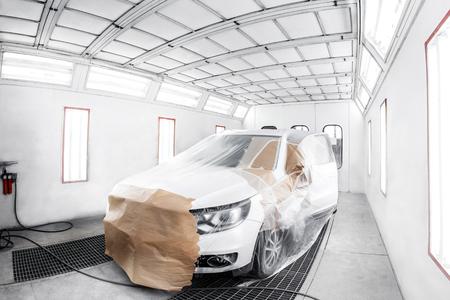 Arbeider die een witte auto in een speciale garage schildert, die een kostuum en een beschermende uitrusting draagt. Stockfoto - 67172737