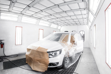 worker painting a white car in a special garage, wearing a costume and protective gear. Standard-Bild