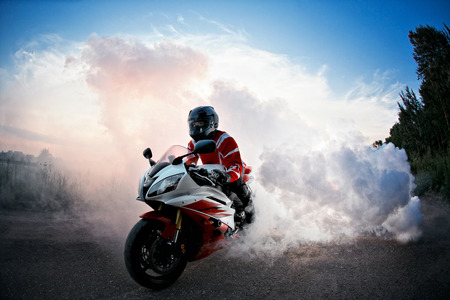 biker staying on bike on road with smoke of the tire, burn out in the moto show Archivio Fotografico